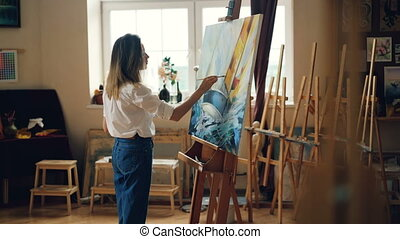 Slender blond girl is painting picture with oil paints...