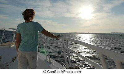 Slender blond woman standing on ship`s bow and looking at...