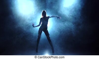 Slender blonde dancer in underwear. Silhouette in smoky, slow motion