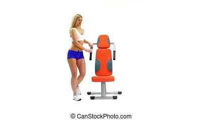 Slender blonde shows exercise on trainer