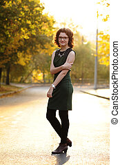 Slender brunette girl in green dress with spectacles in empty street at sunrise
