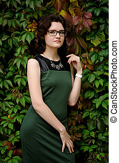 Slender brunette girl in green dress with spectacles in ivy