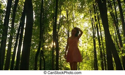 Slender brunette girl in pink dress walks at camera in forest. Steadicam slow motion video