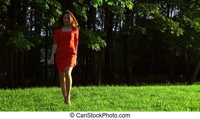 Slender brunette girl in red dress walking on the grass in the park. Slow motion video, 120 fps