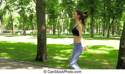 brunette teen jumps rope in the Park