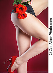 Slender depilated attractive female legs with a rose on a red background. Depilation and foot care.