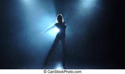 Slender female dancing in smoky studio, slow motion