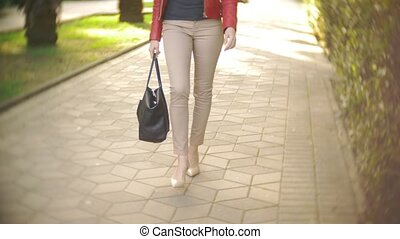 slender female legs in beige trousers and high-heeled shoes...