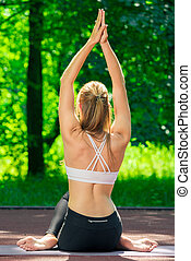 slender girl coach practices yoga in a summer park, view from the back
