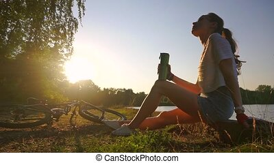 Slender girl cyclist with ponytail hairstyle drinking from...