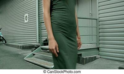 slender girl in a dress tight walks on the street - slender...