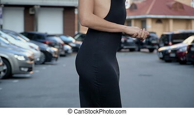 Slender girl in a stylish black dress posing in the parking...