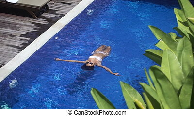 Slender girl in a white bathing suit floating on her back in the pool. Beautiful young woman enjoying vacation at the resort.