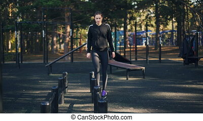 Slender girl is doing aerobic sports outdoors stepping over...