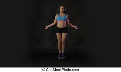 Slender girl jumping rope