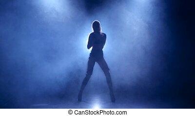 Slender girl pj is dancing in studio in leather underwear