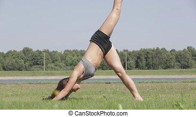 Slender girl practices yoga on the grass