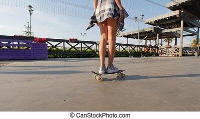 Slender girl rides a skateboard on a beautiful promenade on...