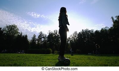 Slender girl riding a gyro on the grass. She's circling. The...