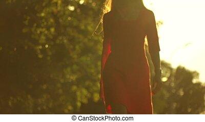Slender girl silhouette walking against sun in the park. ...