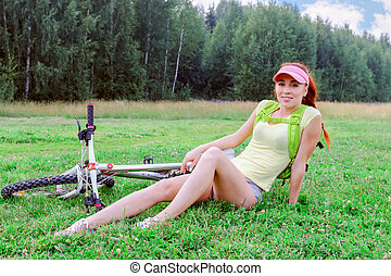 Slender girl with a backpack on his shoulders is sitting on the green grass, lying next to her bike