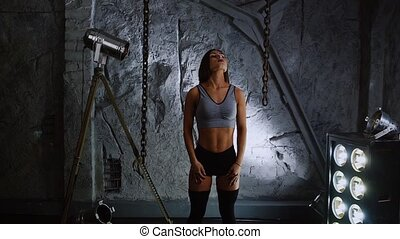 Slender inflated beautiful woman athlete on the background of stone walls conduct warm-up your neck before training.