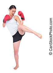 Slender model with boxing gloves kicking while posing on...