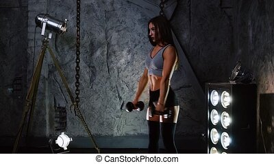 Slender sexy athlete performs exercises with dumbbells to...