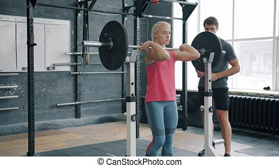 Slender sportswoman in sportswear is squatting with barbell working out with coach in gym busy with weight lifting exercises. People and sports concept.