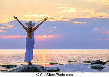 Slender woman enjoying freedom near sea