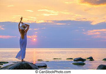 Slender woman in dress enjoying sunset over sea