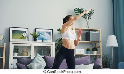 Slender woman in sports clothing exercising at home raising...