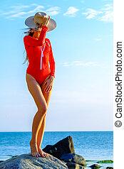 Slender woman in swimsuit at seaside in summer