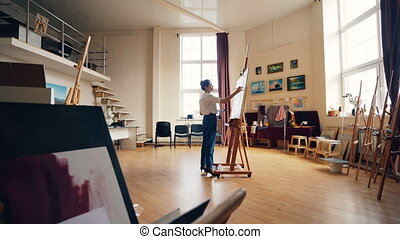 Slender woman is painting on canvas standing in center of...
