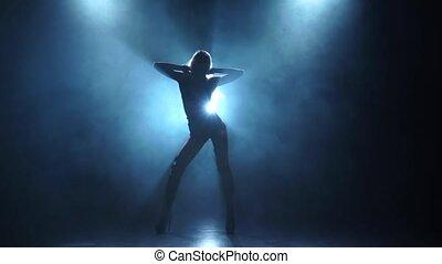 Slender woman pj is dancing in smoky studio, slow motion