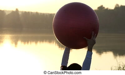 Slender woman raises her fitball while lying at sunset in slo-mo