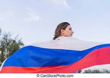 Slender woman runs with the Russian flag behind her back, view from behind. The flag of the Russian Federation beautifully waving in hands of a woman in the wind