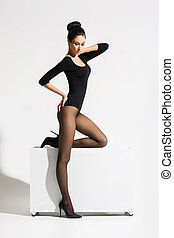 Slender woman with hot legs posing on cube over isolated...
