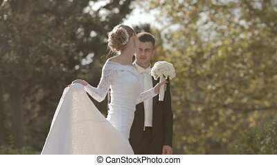 Slender young bride spinning in a park - Slender young bride...