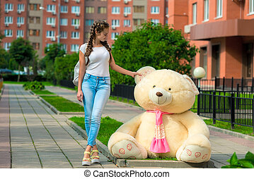 slender young girl and a huge teddy bear on the street in the city