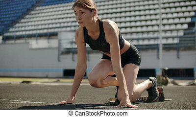 Slender young girl athlete is in position to start running...