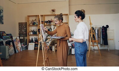 Slender young woman art student is painting working at picture and talking to her friendly teacher standing indoors in modern workshop. Fine arts and education concept.