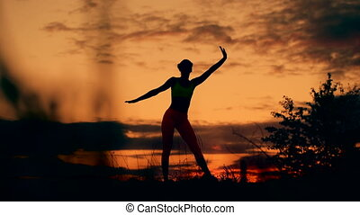 Slender young woman doing fitness exercises in the warm-up at sunset. Flexible shape, smooth motion.