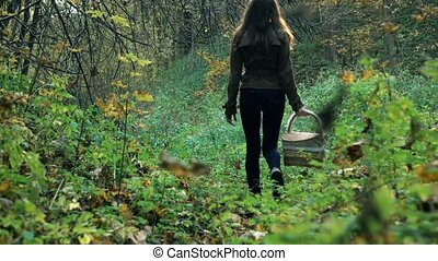 Slender young woman in a brown jacket walking through the forest holding a basket. 4K steadicam shot