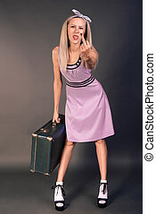 Slender young woman in a pink dress with a suitcase standing...