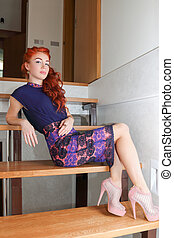 Slender young woman in beautiful dress sitting on the stairs in the house