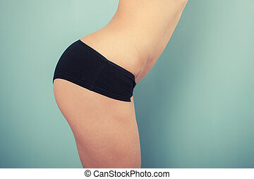 Slender young woman in black underwear