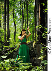 Slender young woman in straight green dress with stick in green forest