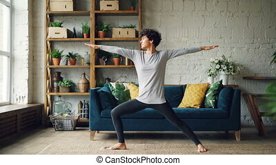 Slender young woman is practising yoga at home standing in...