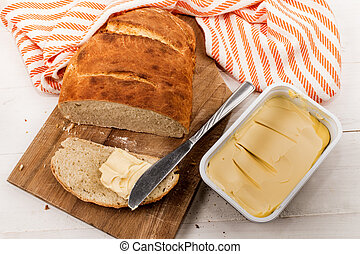 slice home baked bread with margarine on a cutting board